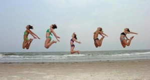 Young ladies jumping on the beach in sync.